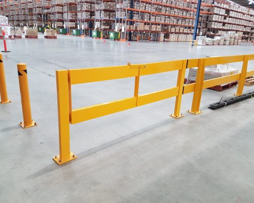 Verge safety barriers. Bollards and double swing gate. Forklift barrier in large warehouse
